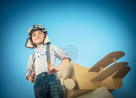 Foto de Little boy with a cardboard airplane outdoors - Imagen libre de derechos