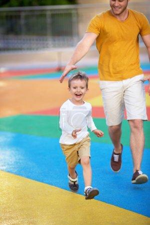 Photo pour Père et fils sur le terrain de jeu - image libre de droit