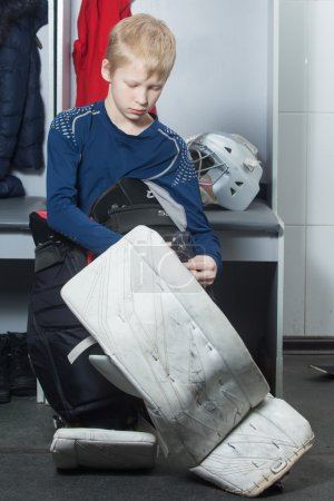 Photo for Young boy in goalie uniform fasten leg pads - Royalty Free Image