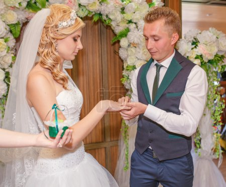 Portrait of handsome groom putting wedding ring on brides hand