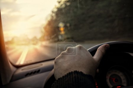 Hand on the steering wheel - the driver drives into the sunset