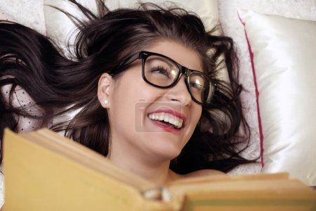 Photo pour Jeune fille lisant un livre dans le lit en riant - image libre de droit