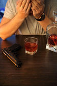 Man crying with gun and alcohol