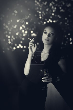 Hauntingly beautiful woman standing with a cigarette in evening gown at the bar