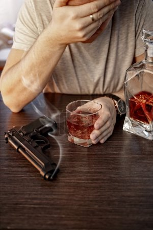 Photo for Devastated man with a gun and alcohol - Royalty Free Image