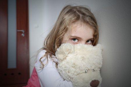 Young sad girl hugging a teddy bear