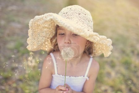 Young girl in a hat blowing dandelion