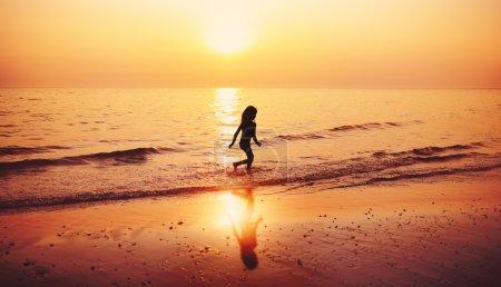 Child running beach during sunset