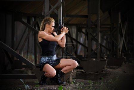 Photo pour Jeune femme en uniforme avec arme à feu (version normale) - image libre de droit