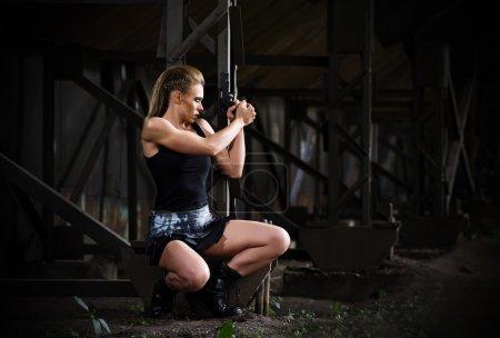 Photo pour Jeune femme en uniforme avec pistolet (version noire) - image libre de droit