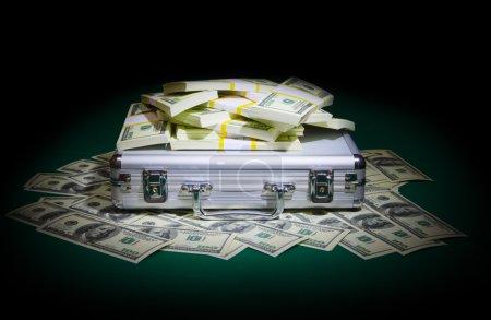 Photo pour Boîtier métallique avec dollars sur table verte - image libre de droit