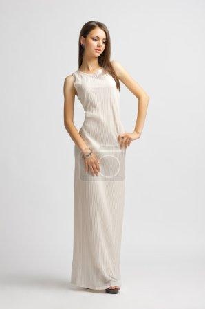 Photo pour Jeune fille en robe longue sur fond gris - image libre de droit