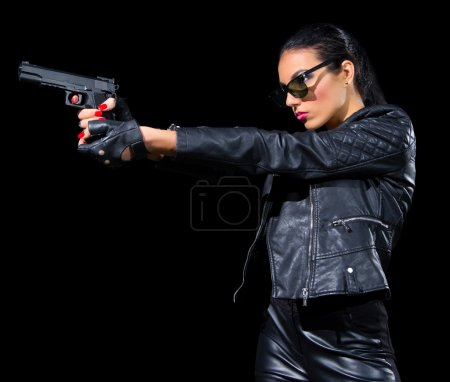 Young woman in leather clothes with gun