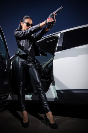 Woman in leather clothes with gun near the car