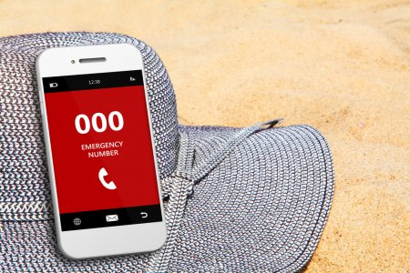 Mobile phone with emergency number 000 on the beach