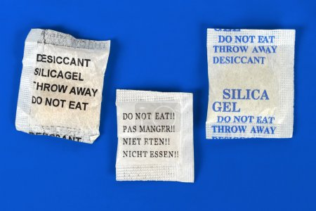 Macro of silica gel bags on blue background...