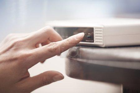 Human hand turning on wireless modem. Close-up hor...