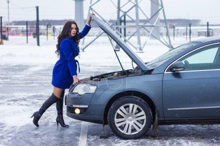 Photo pour Attrayant femme tenant sur le capot de sa voiture - image libre de droit