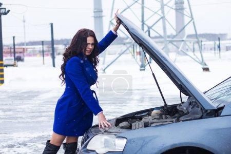 Photo pour Brunette regardant sous le capot de sa voiture - image libre de droit