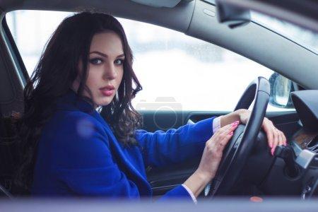 Photo pour Femme attrayante conduisant une voiture sourires amicaux - image libre de droit