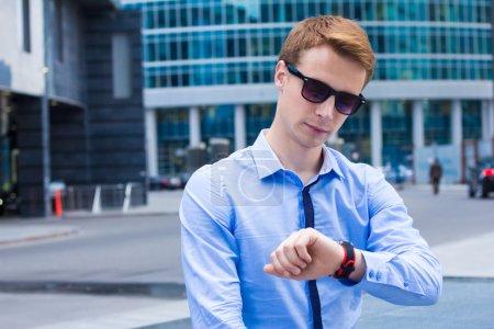 Photo pour Portrait de jeune homme d'affaires en regardant l'horloge et attend le client - image libre de droit