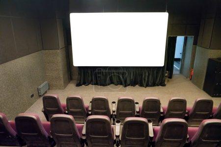 Photo pour Scène vide dans le petit cinéma avec écran blanc isolé - image libre de droit