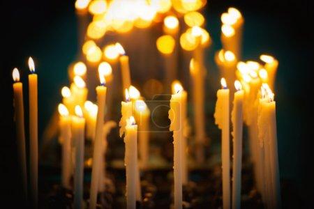 Photo pour Lumière des bougies dans l'église sur le fond noir - image libre de droit