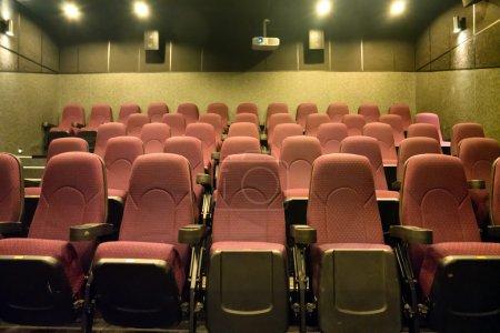 Photo pour Sièges vides dans la petite salle de cinéma avec projecteur de cinéma - image libre de droit