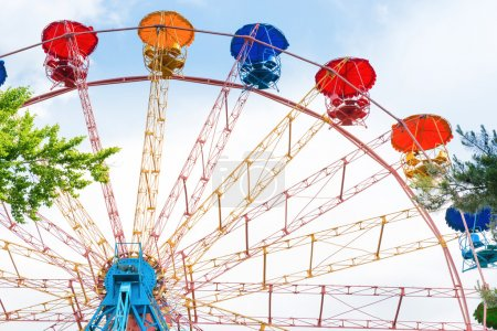 Photo for Ferris wheel in the green park over blue sky with clouds - Royalty Free Image