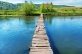 Old wooden bridge through river
