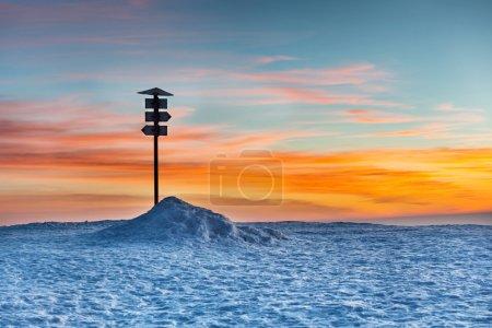 Photo pour Panneau de direction au sommet de la montagne d'hiver contre le coucher du soleil - image libre de droit