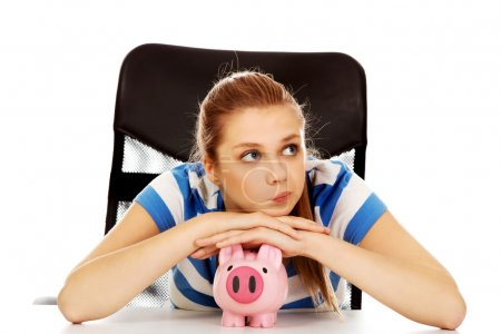 Photo for Teenage woman with piggybank on the table. - Royalty Free Image