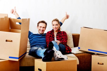 Photo for Happy tired couple sitting on couch in new home with cordboard boxes around. - Royalty Free Image