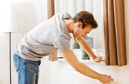 Young man changing temperature of radiator