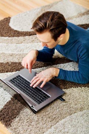 Photo pour Jeune homme couché sur le sol et utilisant un ordinateur portable . - image libre de droit
