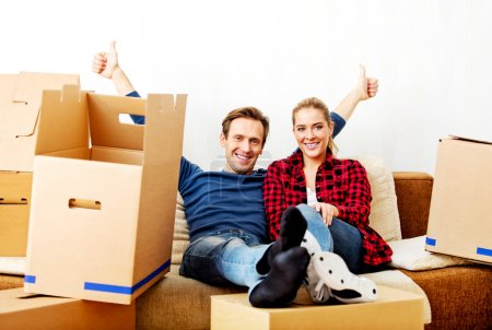 Happy tired couple sitting on couch in new home with cordboard boxes around