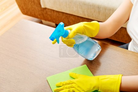 Photo for Young woman cleaning  table in yellow gloves. - Royalty Free Image