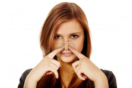 Photo for Young woman pinches nose with fingers hands looks. - Royalty Free Image