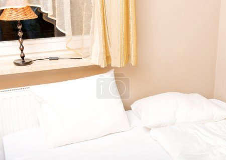 Bed with white bedclothes and brown bedcover