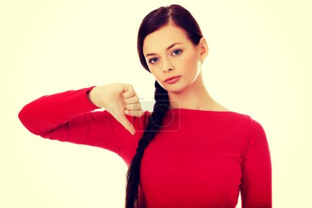 Young unhappy woman with thumb down