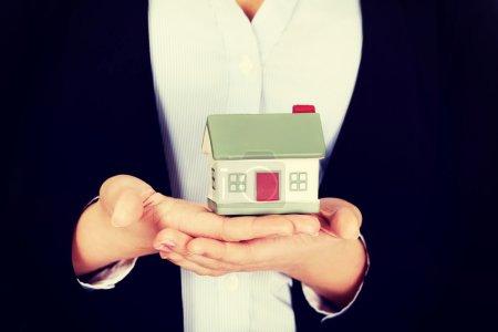 Photo pour Femme d'affaires tenant un modèle de maison. - image libre de droit
