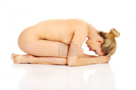 Photo for Young naked woman sitting curled up. - Royalty Free Image