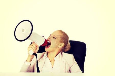 Photo pour Femme d'affaires assis derrière le bureau et criant à travers un mégaphone. - image libre de droit