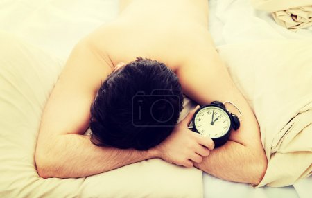 Exhausted man being awakened by an alarm clock.