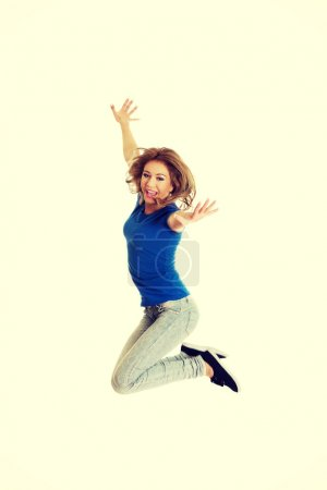 Photo for Young beautiful happy woman jumping. - Royalty Free Image