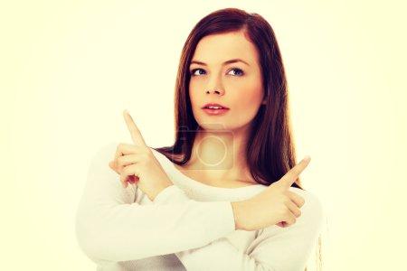 Photo pour Jeune femme confus pointant dans deux directions différentes . - image libre de droit