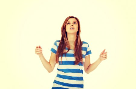 Photo for Teenage woman with outstretched arms looking up. - Royalty Free Image