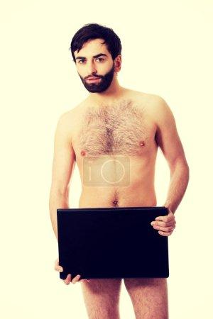 Young shirtless man holding laptop.