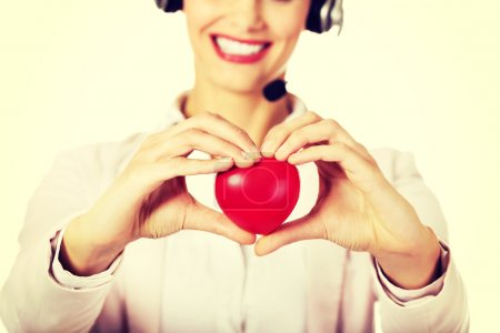 Photo for Happy call center woman holding heart toy. - Royalty Free Image