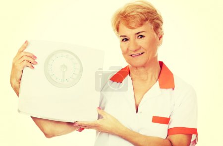 Photo for Smile elderly female doctor or nurse holds weigh scale. - Royalty Free Image